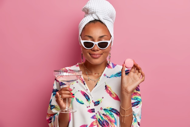 Photo of pleased dark skinned woman closes eyes smiles gently enjoys spending time at home holds delicious macaroon and glasses of martini cocktail wears dressing gown isolated over pink wall