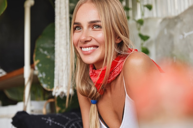Photo of pleased dreamy beautiful young blonde female student wears bandana on neck