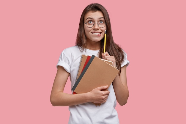 Photo of pleased european young lady looks happily upwards, holds pencil, textbooks, has dreamy expression, writes down notes