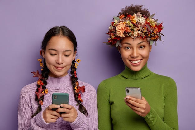 Photo of pleased female friends hold modern smartphones, send messages to friends, use creative way to wear autumn leaves, have glad expressions, wears sweaters.