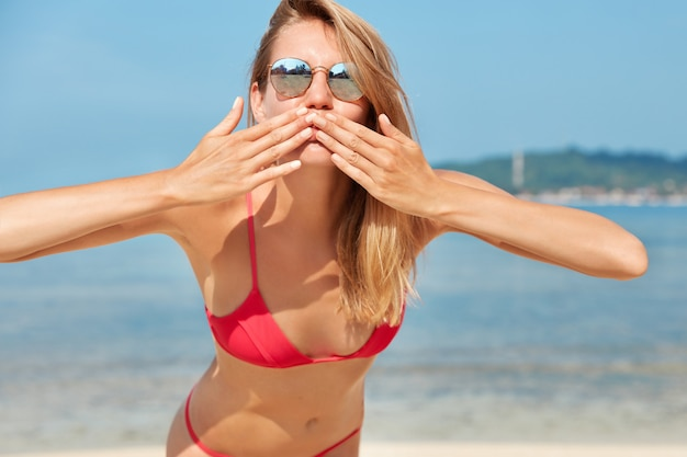 Photo of pleased female tourist in trendy shades, blows air kiss in camera, poses against ocean view against blue horizon, has perfect slim body, recreats at coastline. people, summer and rest