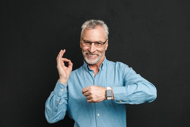 Photo of pleased gentleman 60s with grey hair wearing eyeglasses showing ok sign being on time, isolated over black wall