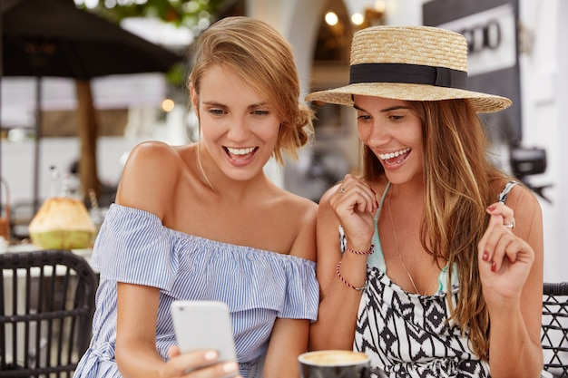 Photo of pleased joyful female friends look happily into cell phone, read good news on website. pleased two women bloggers rejoice great success, have many followers, sit in coffee shop together