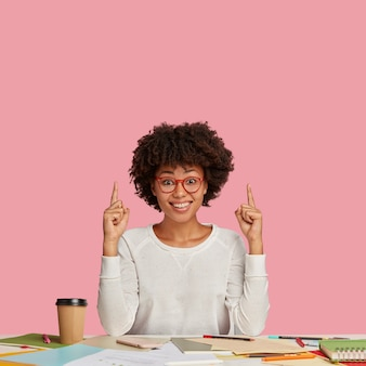 Photo of pleased lovely dark skinned woman poses at coworking space, surrounded with notebook, pen, takeaway coffee, wears glasses, indicated upwards, shows free space for your advertisement.
