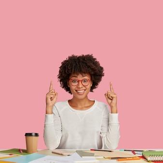 La foto della donna dalla pelle scura adorabile compiaciuta posa nello spazio di coworking, circondata da taccuino, penna, caffè da asporto, porta gli occhiali, indicata verso l'alto, mostra lo spazio libero per la tua pubblicità.