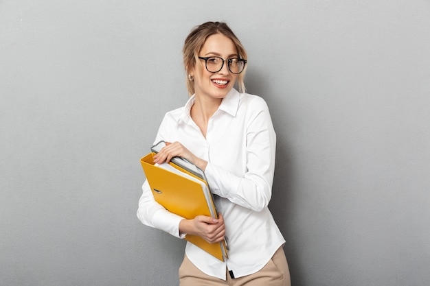 Photo of pleased secretary wearing glasses holding paper folders in the office, isolated