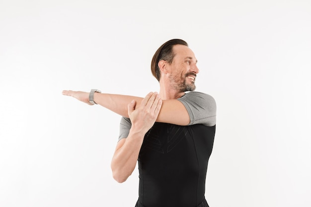 Photo of pleased sportsman 30s wearing smartwatch and t-shirt smiling and stretching arms while warming up