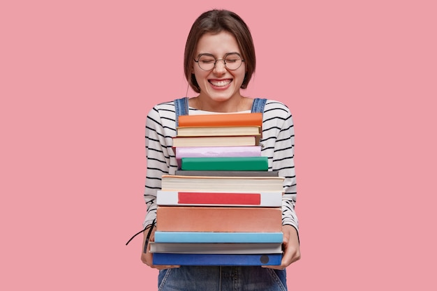 Photo of pleased teenage girl holds heap of textbooks, being in high spirit, wears denim overalls, poses against pink background
