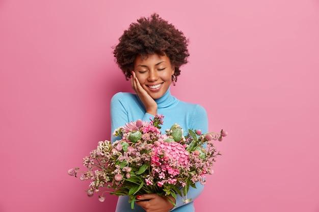 La foto di una giovane donna afroamericana, felicemente toccata, ha ricevuto un regalo per l'anniversario, porta un grande mazzo di fiori, chiude gli occhi e sorride delicatamente, indossa un dolcevita blu,
