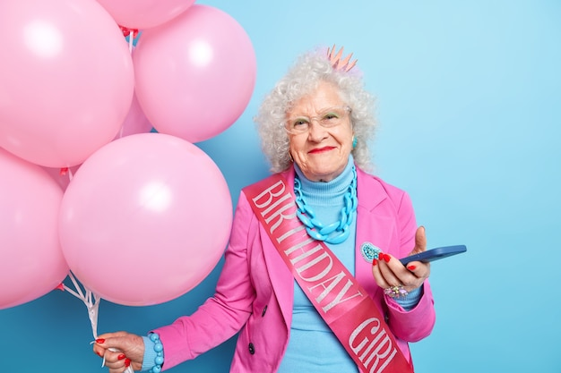 Photo of pleased wrinkled woman enjoys birthday celebration uses modern cellular gets messages of congratulations looks beautiful for her old age holds inflated balloons wears festive clothes