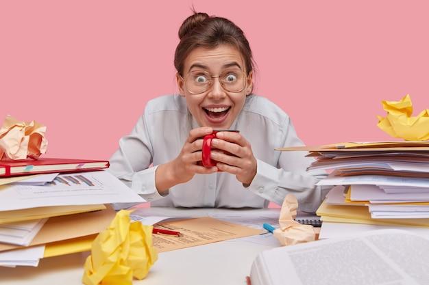 Foto di felice giovane studentessa universitaria indossa occhiali ottici, beve il tè, vestito con una camicia bianca, essendo in alto spirito, occupato a lavorare
