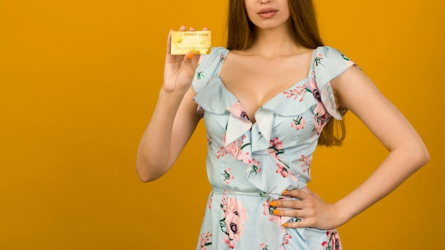 Photo of pleased young woman posing isolated over yellow wall background holding debit or credit card.
