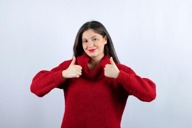 Foto di una giovane donna felice con un maglione rosso che mostra i pollici in su