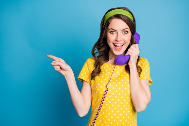 Photo portrait of curly brunette talking on violet telephone pointing finger at copyspace isolated on pastel light blue colored background
