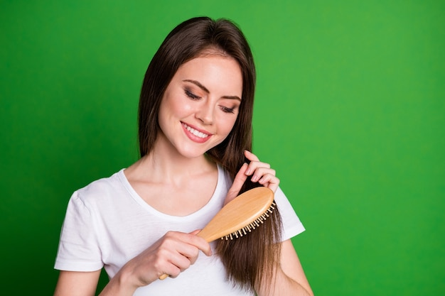 Photo portrait of focused girl brushing hair isolated on vivid green colored background