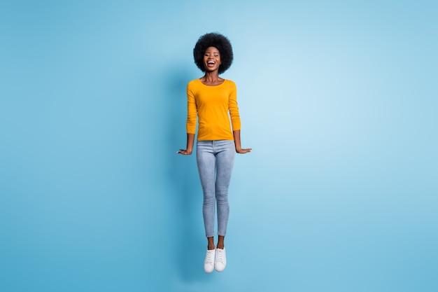 Фото портрет все тело женщины, прыгающей прямо вверх, изолированные на пастельно-синем фоне