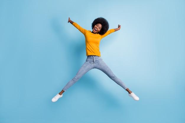 Фотопортрет все тело женщины, прыгающей вверх, распростертой, как звезда, изолирован на пастельно-синем фоне