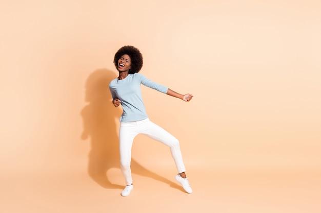 Фото портрет в полный рост афро-американской женщины, танцующей, наслаждаясь вечеринкой, изолированной на пастельно-бежевом фоне