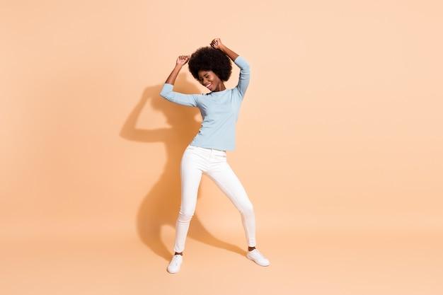 Фото портрет в полный рост афро-американской женщины, танцующей руки над головой, изолированные на пастельно-бежевом фоне