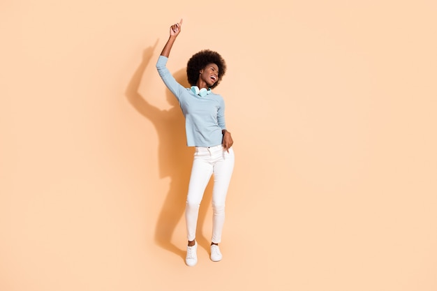 Фотопортрет в полный рост беззаботной темнокожей женщины, танцующей в наушниках на шее, одним пальцем вверх, изолированным на пастельно-бежевом фоне
