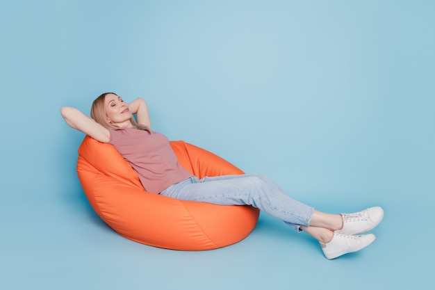 Photo portrait full body view of sitting in orange bean bag chair rest relax sleep nap time isolated on blue colored background