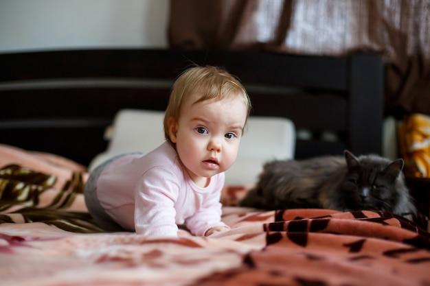 그녀는 침대에 크롤링 핑크 뺨을 가진 여자 아기의 사진 초상화. 집에 앉아있는 아이