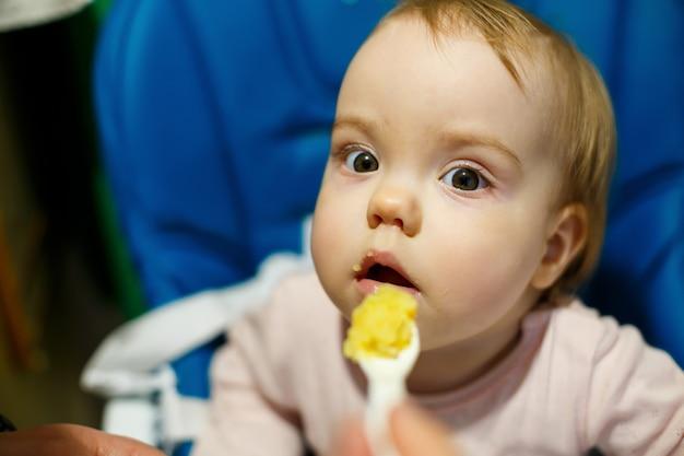 분홍색 볼을 가진 여자 아기의 사진 초상화는 먹이를 주기 위해 의자에 앉아 죽을 먹습니다. 집에 앉아있는 아이