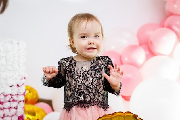 ピンクの風船とピンクのドレスを着た1歳の誕生日の女の子の写真の肖像画。休日の子供は笑顔、子供の感情。誕生日会