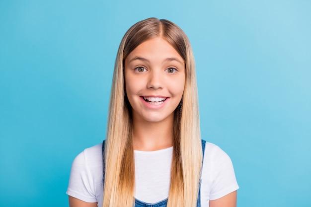 Фотопортрет очаровательного слегка удивленного ребенка, изолированного на пастельно-синем фоне