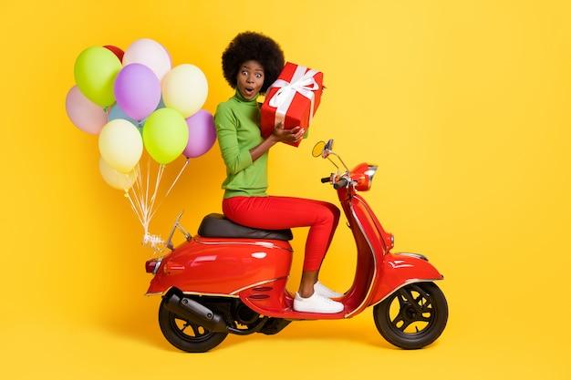 Фотопортрет афроамериканской девушки, держащей коробку и гадающей, что внутри, в повседневном зеленом пуловере на красном велосипеде с воздушными шариками, изолированными на ярко-желтом фоне
