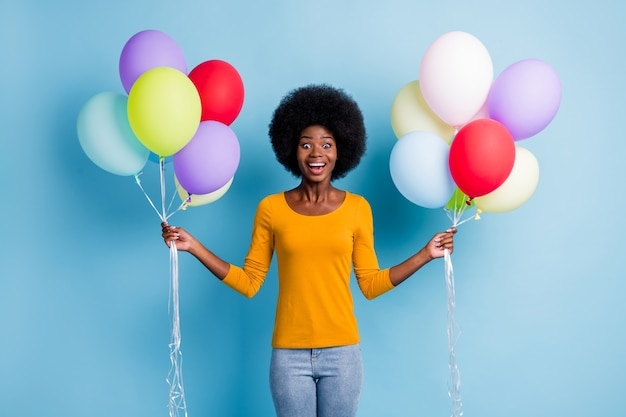 Фотопортрет изумленной счастливой темнокожей девушки, держащей груду разноцветных воздушных шаров, смеясь, изолированную на ярком синем фоне