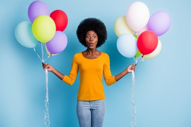 Фотопортрет изумленной девушки с черной кожей, держащей кучу разноцветных воздушных шаров на ярком синем фоне