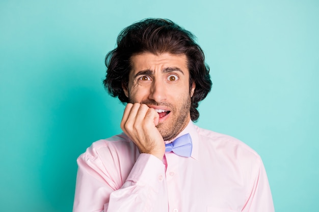 Фотопортрет озабоченного мужчины, кусающего ногти, изолированного на пастельно-голубом фоне