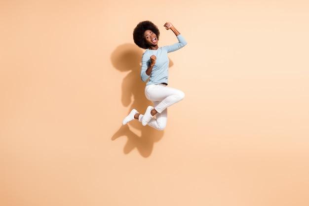 파스텔 베이지색 배경에 격리된 환호성을 지르며 점프하는 놀란 아프리카계 미국인 소녀의 사진 초상화