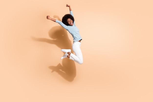 파스텔 베이지 색 배경에 고립 된 비명을 지르며 공중에서 두 주먹을 높이 점프하는 검은 피부 소녀의 사진 초상화