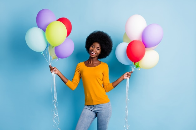 Фотопортрет чернокожей девушки, держащей кучу смеющихся воздушных шаров, изолированную на ярком синем цветном фоне