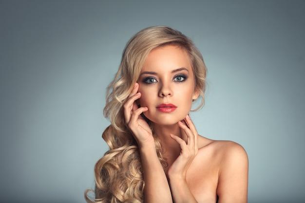 青い背景の上の金髪の女性の写真の肖像画