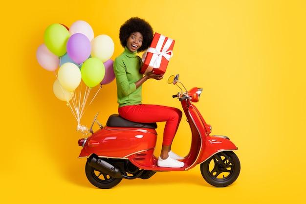 Фото портрет брюнетки афро-американской девушки, держащей красный завернутый подарок на велосипеде с воздушными шарами, изолированном на ярко-желтом цветном фоне