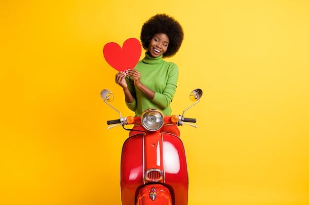 선명한 노란색 배경에 격리된 빨간색 하트 컷을 들고 자전거를 탄 캐주얼한 검은색 갈색 머리 여성의 사진 초상화