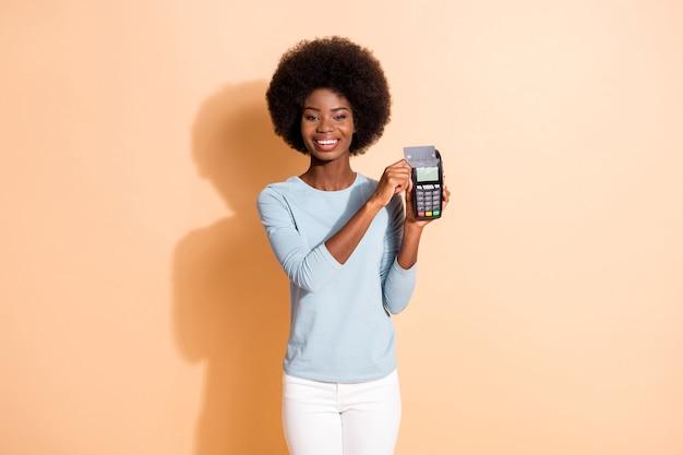 곱슬곱슬한 피부를 가진 소녀의 사진 초상화는 베이지색 배경에 격리된 현금 없는 구매를 하는 은행 터미널에 신용 카드를 넣었다