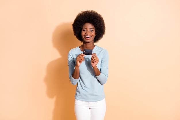 ベージュ色の背景で隔離の青いシャツを着てプラスチックの銀行カードを示す暗い肌の巻き毛の幸せな陽気な女の子の写真の肖像画