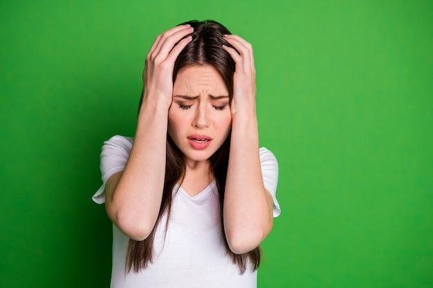 생생한 녹색 배경에 고립 된 두 손으로 머리를 잡고 우울 우는 여자의 사진 초상화