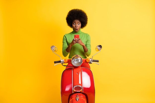鮮やかな黄色の背景で隔離のカジュアルな緑のジャンパーを身に着けている両手で携帯電話を保持しているオートバイの興奮したバイカーライダードライバーの写真の肖像画