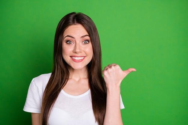 생생한 녹색 배경에 고립 된 측면에 엄지손가락을 가리키는 흥분된 여자의 사진 초상화