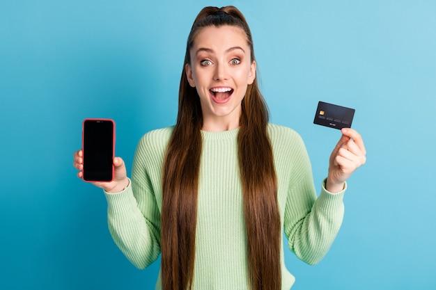 파스텔 블루 색상의 배경에 격리된 녹색 풀오버를 입은 빈 공간 은행 카드가 있는 전화를 들고 입을 벌리고 있는 흥분한 소녀의 사진 초상화