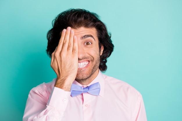 파스텔 청록색 배경에 격리된 한 손바닥 뒤에 반 얼굴을 숨기고 있는 남자의 사진 초상화