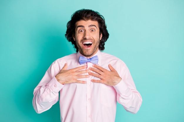 두 손으로 가슴을 만지는 남자의 사진 초상화는 파스텔 청록색 배경에서 격리되어 선택됩니다.