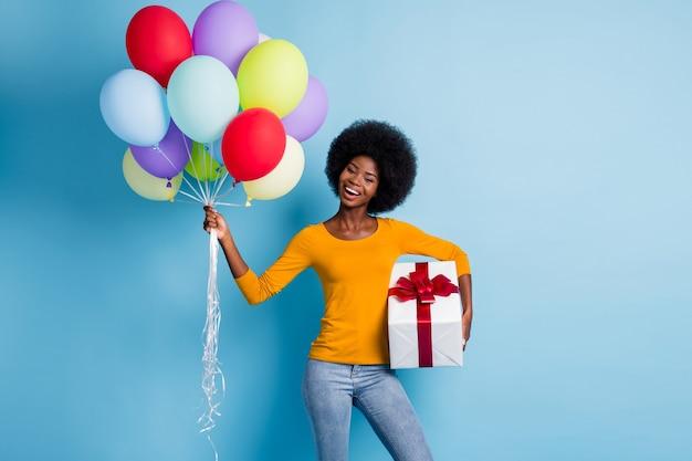 Фотопортрет счастливой темнокожей девушки, держащей груду разноцветных шаров, обернутых настоящим подарком, изолированным на ярком синем цветном фоне