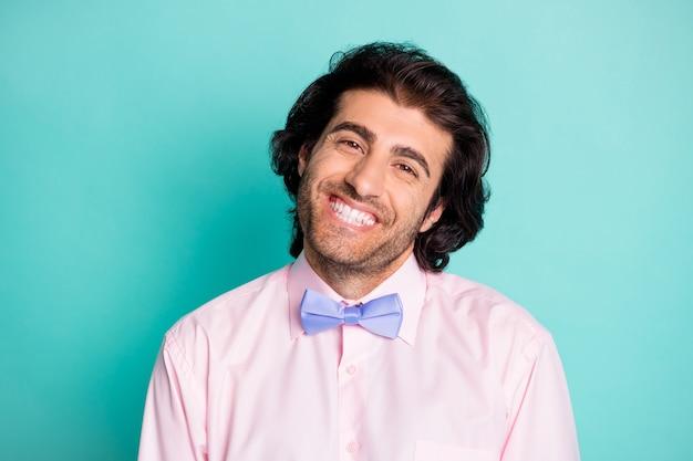 파스텔 청록색 배경에 격리된 측면으로 머리를 기울이고 웃고 있는 행복한 남자의 사진 초상화