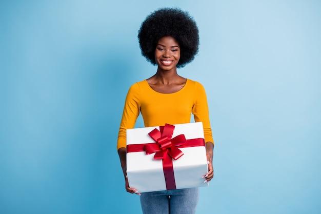 Фотопортрет счастливой улыбающейся чернокожей женщины, держащей обернутый красной лентой подарок на ярком синем фоне